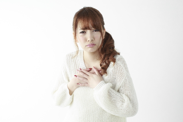 胸を抑える女性 痛み